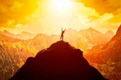 Happy woman on peak of the mountain enjoying the success, freedom and bright future.